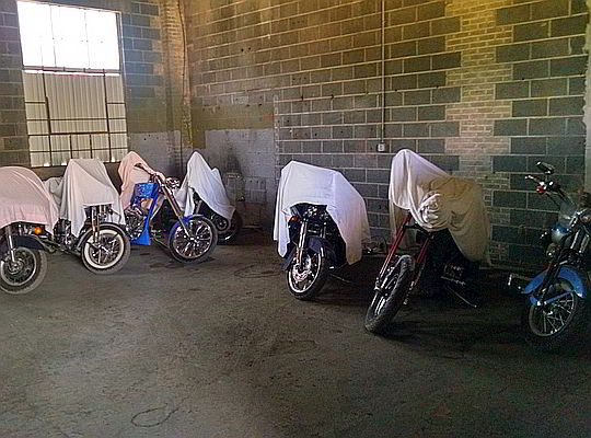 Motorcycles stored indoors and covered with protective tarps