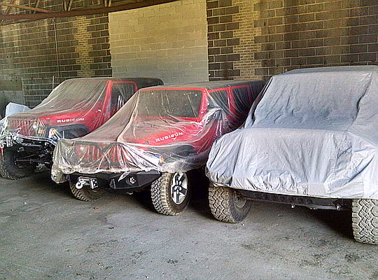 Cars, Jeeps & SUVs in warehouse storage covered with tarps