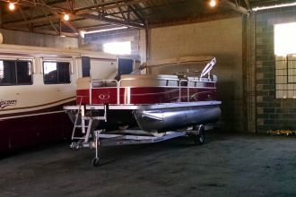 Red pontoon boat in warehouse storage