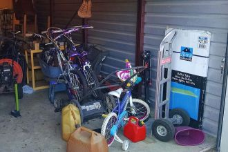 Various household goods in storage unit including bicycles, lawn equipment & various personal items