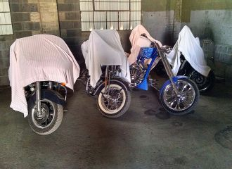 Motorcycles protected with drop cloths parked in warehouse storage facility