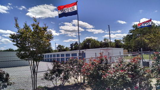 Flags flying over mini storage units
