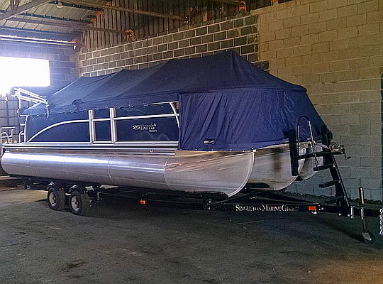 Pontoon boat stored inside and covered with blue tarp
