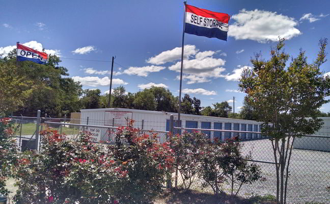 10 x 35 Storage Units in Montgomery, AL - entrance to storage units with self-storage flags waving