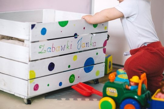 Child searching through toy storage box