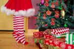 Christmas elf dressed in red and white standing on tiptoes next to tree and holiday gifts