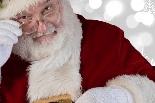 Santa Claus peering over his eyeglasses with an inquisitive expression