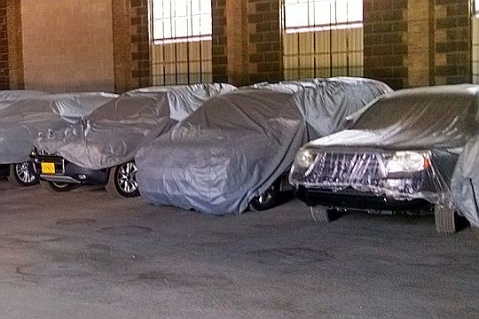 Several cars in storage covered with tarps